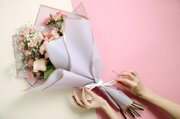 Bouquet di fiori in sfondo rosa e nudo. vista dall'alto sulla donna decora un bouquet Foto Premium