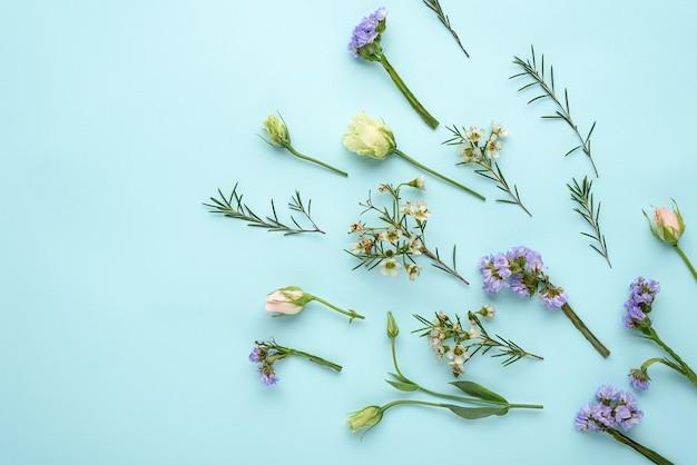 Composizione di fiori di rose, eustoma e citronella sull'azzurro Foto Premium
