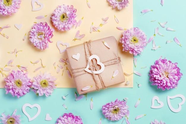 Composizione di fiori con cuori e confezione regalo su uno sfondo rosa pastello Foto Premium