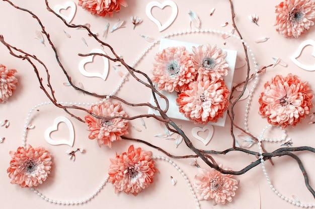 Composizione di fiori con cuori su uno sfondo rosa pastello Foto Premium