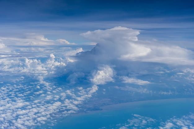Volare sopra la terra e sopra le nuvole nel territorio di singapore. vista dalla finestra dell'aeroplano. l'aereo vola nel cielo sopra la terra. Foto Premium