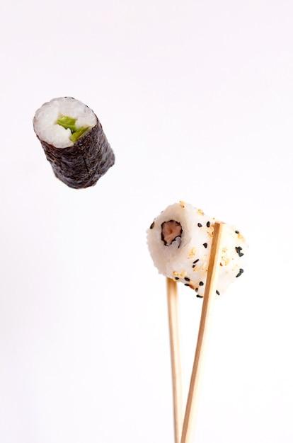 Sushi volante su sfondo bianco, gustosi rotoli di sushi, avocado e bacchette Foto Premium