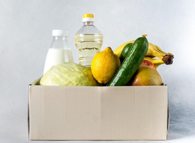 Concetto di donazione dell'alimento di donazione della scatola di consegna dell'alimento. scatola di donazione con verdure, frutta e altri alimenti per le persone Foto Premium
