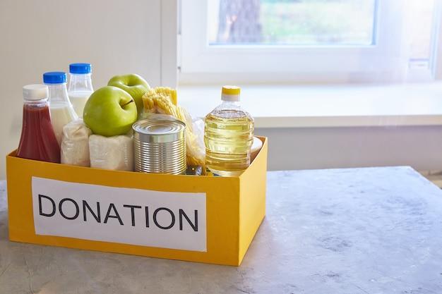 Donazione di cibo in una scatola su un tavolo vicino a una finestra in cucina a casa. per i poveri e i poveri durante la crisi globale. Foto Premium