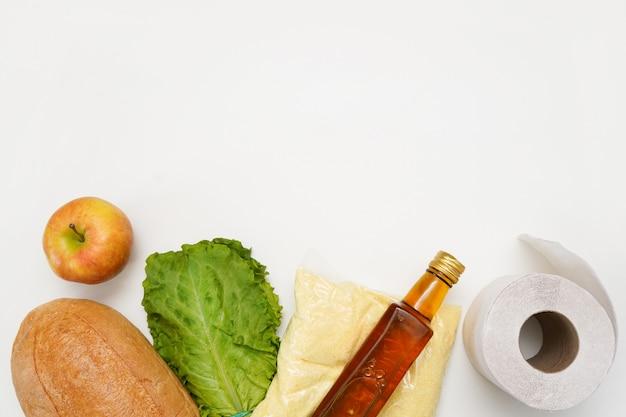 Donazioni di cibo in una borsa sul muro bianco. concetto di consegna del prodotto. fornire prodotti alimentari vitali Foto Premium