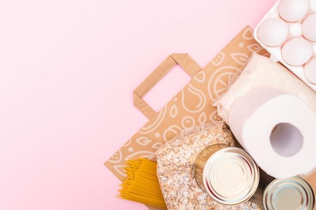 Il cibo per il periodo di isolamento in quarantena disteso su uno spazio giallo con spazio di copia. uova, pasta, fagioli, carta igienica, mela e alcuni seleals. crisi alimentare. Foto Premium