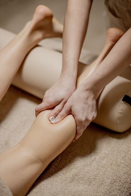 Massaggio ai piedi nella sala massaggi - mani femminili massaggiano i piedi femminili - bellezza e salute. Foto Premium
