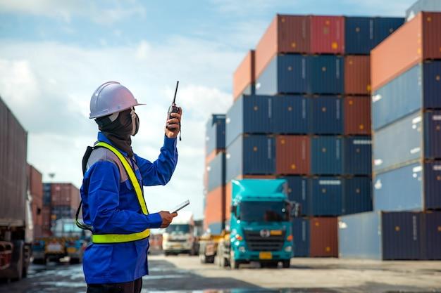 Foreman usa e parla walkie-talkie per controllare il caricamento di container box su camion presso la stazione di deposito container per l'importazione logistica import export Foto Premium