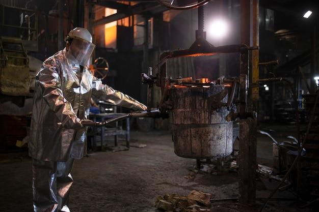Operaio di fonderia che lavora con ferro liquido caldo in fonderia per la produzione di acciaio e metallurgia. Foto Premium