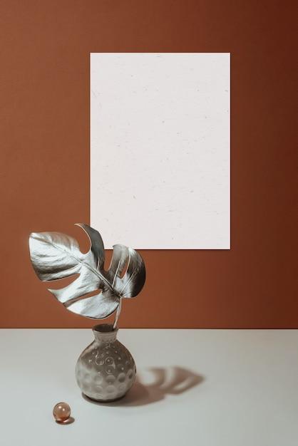 Mockup di cornice e monstera foglia in un vaso su uno sfondo di muro in terracotta. natura morta con ombrelloni. Foto Premium