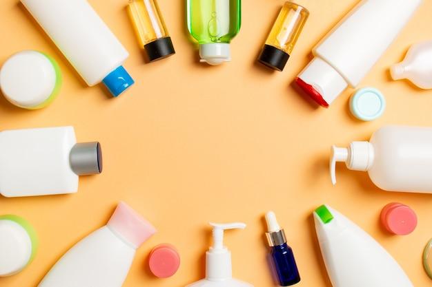 Cornice della bottiglia di plastica per la cura del corpo composizione piatta con prodotti cosmetici Foto Premium