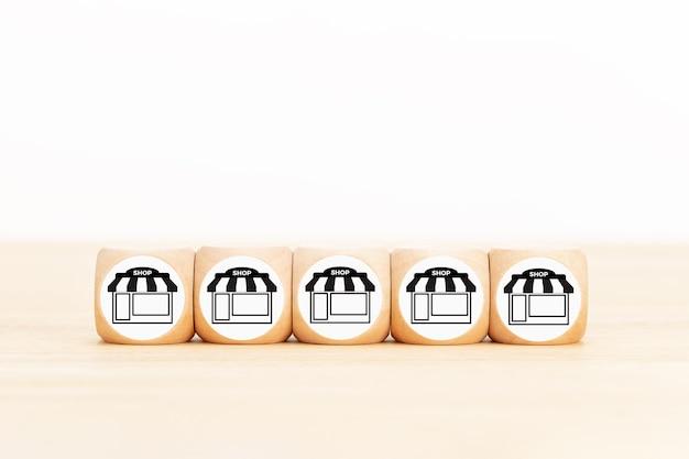 Concetto di business in franchising. mano di uomo d'affari sceglie blocco di legno con icona di marketing in franchising store. copia spazio Foto Premium