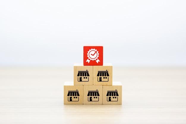 Deposito delle icone di affari di franchising sul blocchetto del giocattolo e sul simbolo di legno di qualità. Foto Premium