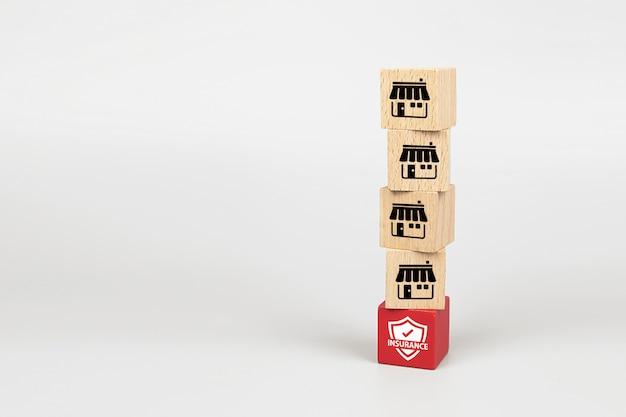 Icone di marketing in franchising negozio sul cubo blog giocattolo di legno è impilato con la base dell'icona di assicurazione. Foto Premium