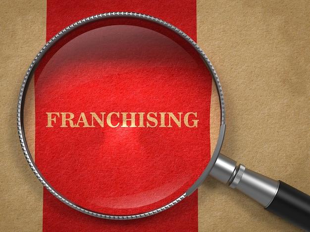 Concetto di franchising. lente d'ingrandimento su carta vecchia con sfondo rosso linea verticale. Foto Premium