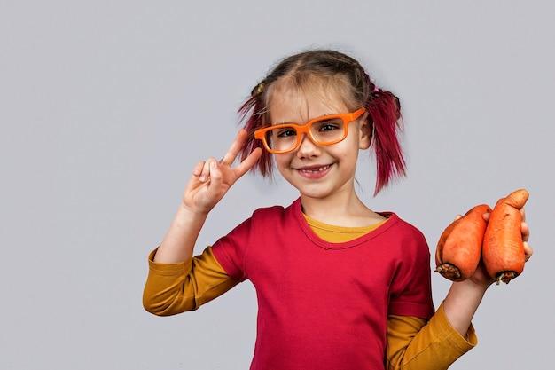 Il ragazzino bizzarro detiene frutta e verdura di colore sbagliato deforme, concetto di cibo di scarto Foto Premium