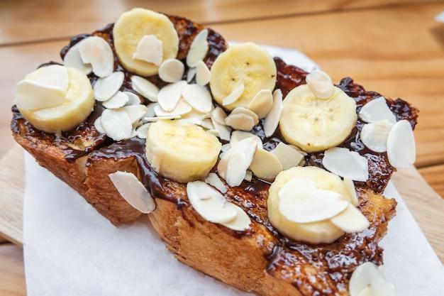 French toast con cioccolato banana fragola e mandorla sul tavolo di legno Foto Premium