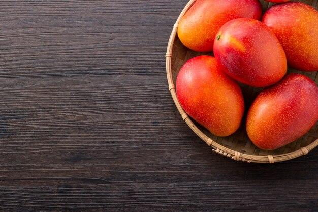 Frutto di mango fresco e bello in un cesto di bambù su uno sfondo di legno scuro, copia spazio (spazio testo), vuoto per il testo, vista dall'alto. Foto Premium