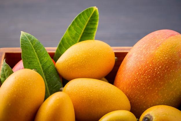 Fresco e bellissimo mango set di frutta in una scatola di legno su uno sfondo di legno scuro, copia spazio (spazio testo), vuoto per il testo Foto Premium