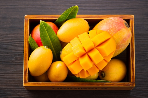 Fresco e bellissimo frutto di mango impostato in una scatola di legno con fette di mango a dadini pezzi su un legno scuro dello sfondo, copia spazio (spazio testo), vuoto per il testo Foto Premium