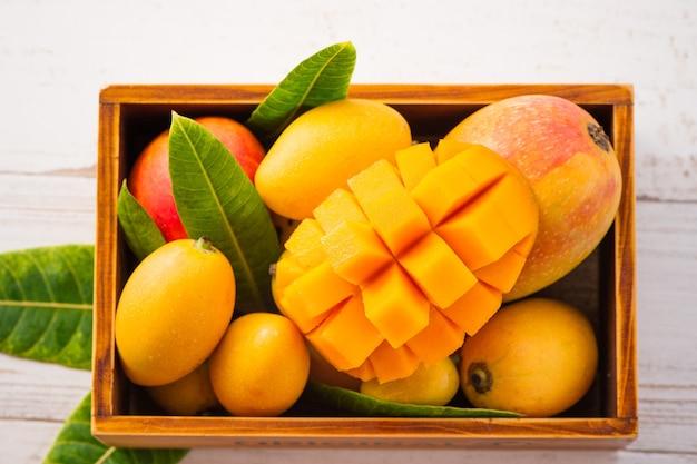 Fresco e bellissimo frutto di mango impostato in una scatola di legno con fette di mango a dadini pezzi su uno sfondo di legno chiaro, copia spazio (spazio testo), vuoto per il testo Foto Premium