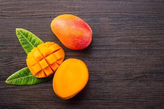 Frutto di mango fresco e bello con pezzi di mango tagliati a dadini su uno sfondo di legno scuro, copia spazio (spazio testo), vuoto per testo, vista dall'alto. Foto Premium