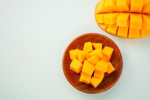 Frutto di mango fresco e bello con pezzi di mango a dadini affettati su uno sfondo azzurro, copia spazio (spazio testo), vuoto per testo, vista dall'alto. Foto Premium