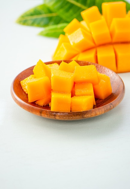 Frutto di mango fresco e bello con pezzi di mango tagliati a dadini su uno sfondo azzurro, copia spazio (spazio testo), vuoto per il testo. Foto Premium