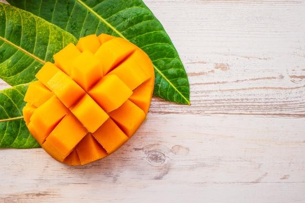 Frutto di mango fresco e bello con pezzi di mango tagliati a dadini su uno sfondo di legno chiaro, copia spazio (spazio testo), vuoto per testo, vista dall'alto. Foto Premium