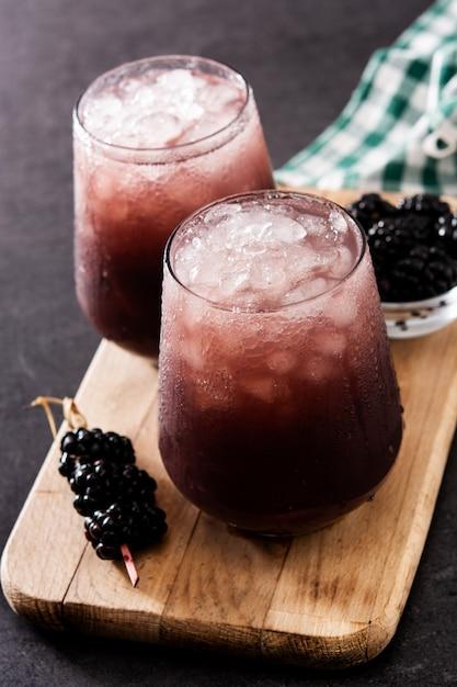 Blackberry cocktail fresco in vetro freddo sul nero Foto Premium
