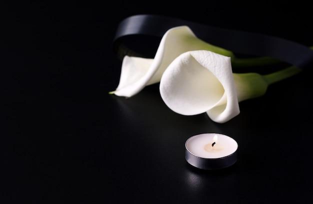 Fiore di calla fresco accanto alle candele sul nero Foto Premium
