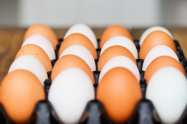 Uova di gallina fresche e uova di anatra nella casella sulla tavola di legno Foto Premium