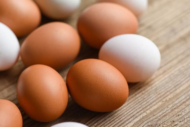 Uova di gallina fresche e uova di anatra sulla tavola di legno / uovo bianco e marrone Foto Premium