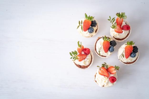 Cupcakes freschi e deliziosi con crema di yogurt, frutti di bosco freschi. muffin alla panna. Foto Premium