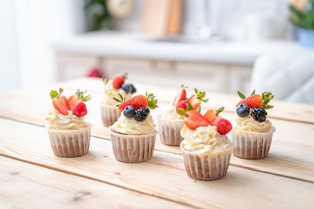 Cupcakes freschi e deliziosi con crema di yogurt e frutti di bosco freschi. Foto Premium
