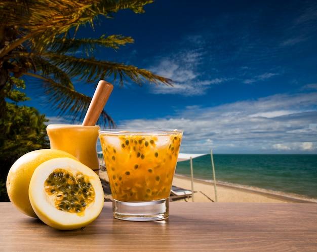 Bevanda fresca a base di frutto della passione caipirinha in spiaggia Foto Premium