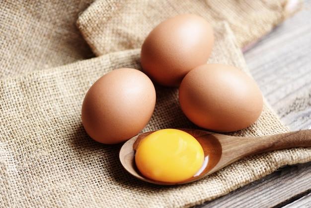Tuorlo d'uovo fresco sul cucchiaio di legno con uova di gallina raccogliere dalla fattoria Foto Premium