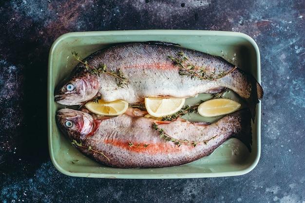 Pesce fresco prima della cottura, condito con erbe aromatiche, pepe, timo e limone. Foto Premium