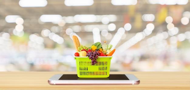 Cibo fresco e verdure nel carrello sullo smartphone mobile sulla tavola di legno Foto Premium
