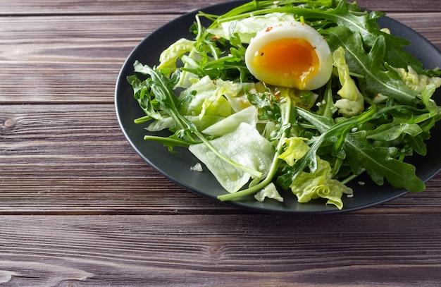 Insalata verde fresca con uovo su sfondo di legno. Foto Premium