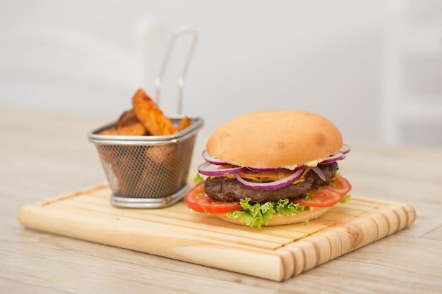 Hamburger fresco fatto in casa sul piccolo tagliere con patate alla griglia, servito con salsa ketchup e sale marino sul tavolo di legno con fondo di legno grigio. Foto Premium
