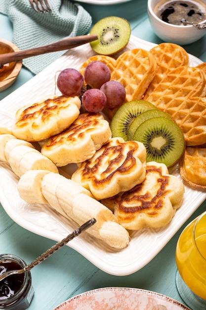 Frittelle di fiori caldi freschi con cuori di cialde, marmellata di frutti di bosco e frutta sulla superficie turchese. concetto di cibo sano Foto Premium