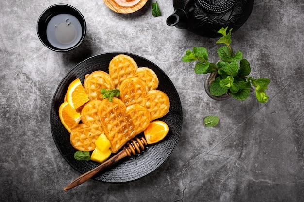 Cuori di cialde calde fresche con fette di arancia e miele su superficie grigia, vista dall'alto, piatto. una sana colazione cibo concetto Foto Premium