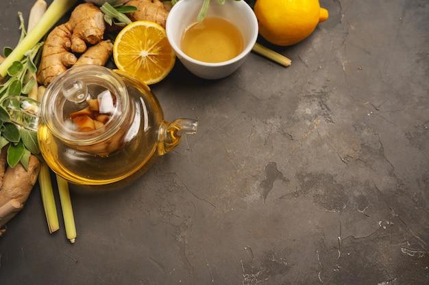 Ingredienti freschi zenzero, citronella, salvia, miele e limone per un tè antiossidante e antinfiammatorio sano su sfondo scuro con spazio di copia. vista dall'alto. Foto Premium
