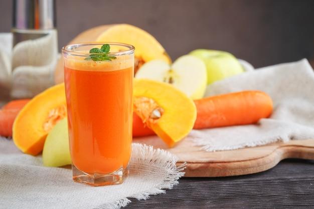 Succo di frutta fresco, mix di frutta e verdura su un tavolo di legno Foto Premium