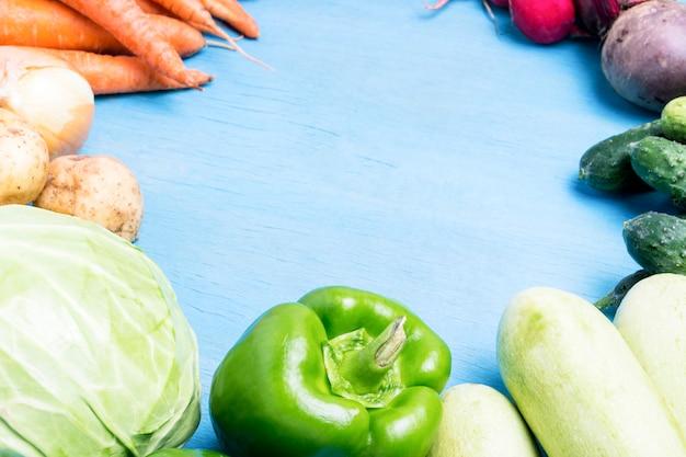 Verdure fresche dell'azienda agricola organica, sanità, su un fondo di legno blu. raccogliere. stile country. forma del cerchio. concetto di fiera agricola. vista piana, vista dall'alto Foto Premium