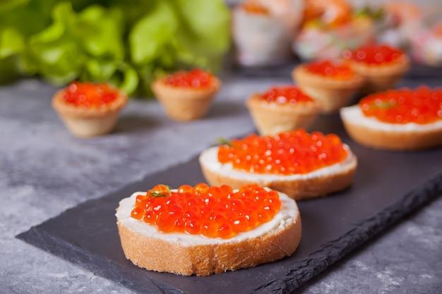 Caviale rosso fresco su pane sulla banda nera. panini con caviale rosso. Foto Premium