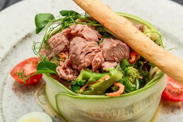 Insalata fresca di tonno, cetriolo, uova di quaglia e verdure su fondo nero Foto Premium