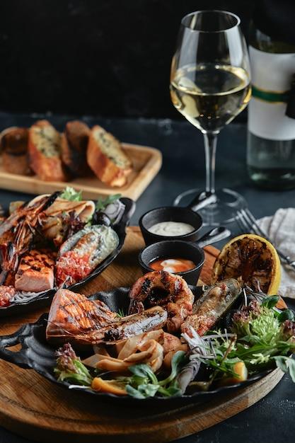 Frutti di mare freschi e vino bianco su un tavolo di pietra. ostriche, gamberi e capesante, calamari, serviti dallo chef, ben disposti su piatti, spazio di cemento scuro. Foto Premium
