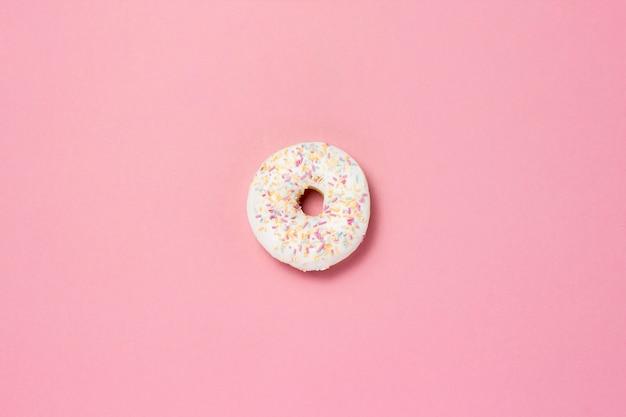 Ciambella dolce saporita fresca su un fondo rosa. il concetto di fast food, prodotti da forno, colazione, dolci. minimalismo. vista piana, vista dall'alto. Foto Premium
